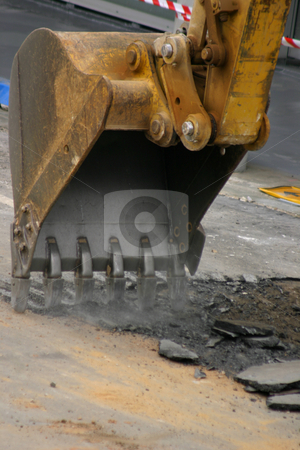 Roadwork - Digging up the Road stock photo, Large steel teeth of the excavator vibrate and shake noisily as they begin to dig up an existing road. by Leah-Anne Thompson