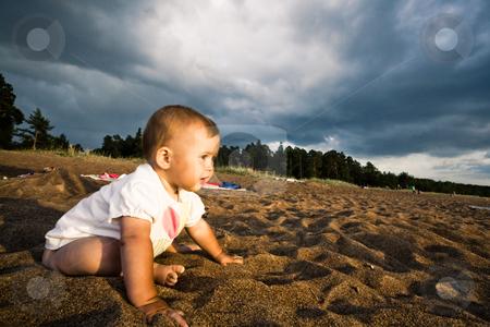 On a beach stock photo, Cute baby sitting on a beach under the thunder sky by Alexandr Vikulov