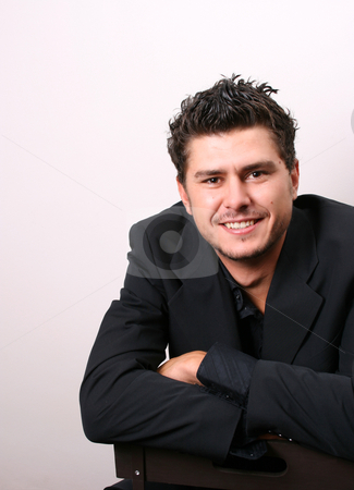 Smiling Male Model stock photo, Male model in studio against white wall by Vanessa Van Rensburg