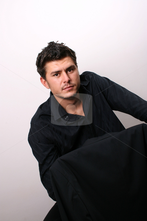 Male Model on chair stock photo, Male model in studio against white wall by Vanessa Van Rensburg