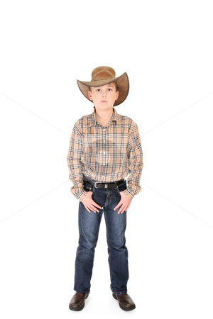 Young cowboy on white background stock photo, A young cowboy standing with feet apart on a white background. by Leah-Anne Thompson