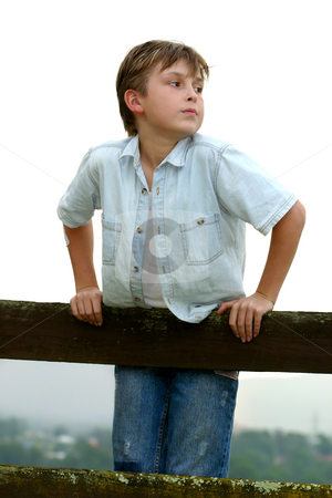 Child leaning on a fence stock photo, Child standing on a timber post and rail fence on an overcast afternoon. by Leah-Anne Thompson