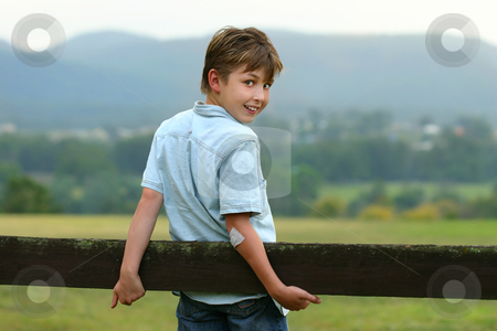 Down on the farm stock photo, A young happy boy in the paddock on an overcast afternoon. f 3.5 by Leah-Anne Thompson