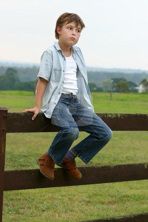 Country boy sitting on a fence stock photo, Farm boy sitting on a wooden fence in late afternoon dusk. Soft. by Leah-Anne Thompson