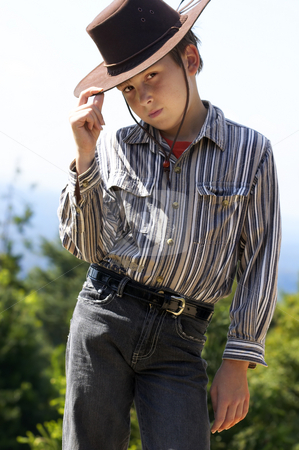 Country boy tipping his hat stock photo, A courteous country boy in denim jeans and button shirt tips his hat. by Leah-Anne Thompson
