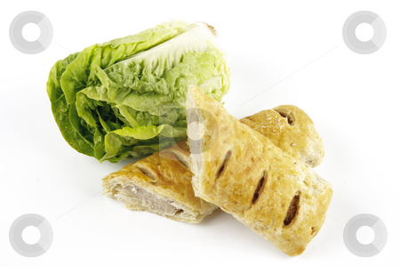 Salad Lettace and Sausage Roll stock photo, Contradiction between healthy food and junk food using a green salad lettace and sausage roll on a reflective white background by Keith Wilson