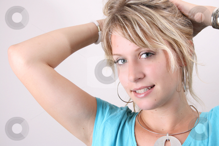 Tying Hair stock photo, Blonde Female model taking up her hair to tie with a hair band by Vanessa Van Rensburg