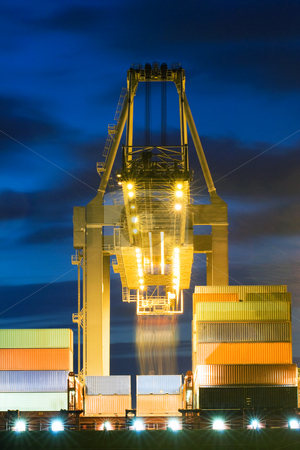 Unloading stock photo, Huge crane unloading containers from a container ship at dusk by Corepics VOF