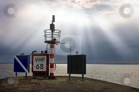 Harbor entrance beacon stock photo, Signs and radio beacon at the end of a pier with navigation lights for shipping at a harbor entrance by Corepics VOF