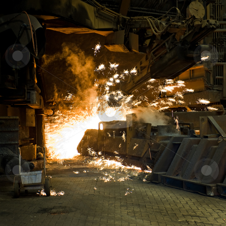 Industrial furnace stock photo, Huge drill creating a pouring hole in an industrial furnace - sparks flying everywhere by Corepics VOF