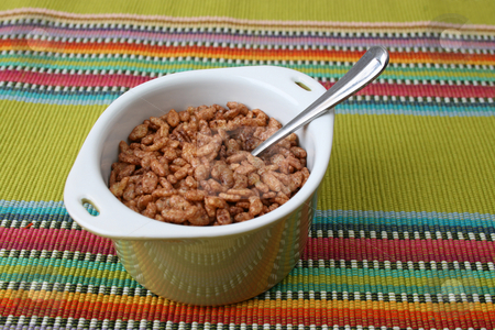 Breakfast Cereal stock photo, Cereal in a green bowl on a colorful placemat by Vanessa Van Rensburg