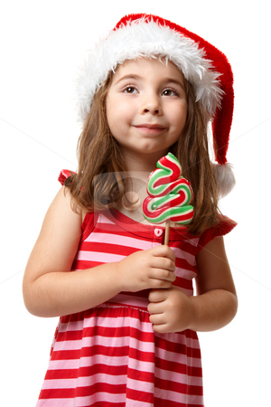Pretty santa girl with christmas lollipop stock photo, Little girl wearing a  red santa hat and striped dress.  She is holding a christmas tree lollipop candy on a stick by Leah-Anne Thompson