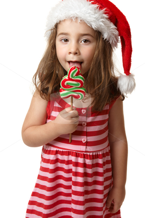 Santa girl licking Christmas tree lollipop candy stock photo, A preschooler wearing a red santa hat is holding a red, white and green christmas tree shaped lollipop candy and licking it by Leah-Anne Thompson