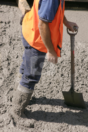 Stuck in cement stock photo, This construction worker stands in wet cement with knee high boots  covered in cement.  He is leaning on his his shovel by Leah-Anne Thompson