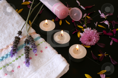 Pink Lotion stock photo, Pink body lotion in a tube next to a hand towel and candles by Vanessa Van Rensburg