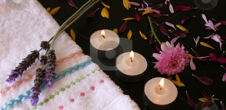 Three Lavender Flowers stock photo, Lavender flowers on a hand towel next to candles with petals spread by Vanessa Van Rensburg