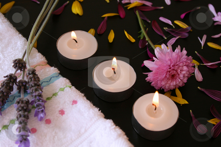 Three flames stock photo, Three teelights next to a hand towel with fresh flowers and petals by Vanessa Van Rensburg