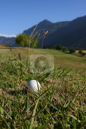 Golf Ball on Course stock photo, Golf Ball on a golf course with a mountain range in the background by Vanessa Van Rensburg