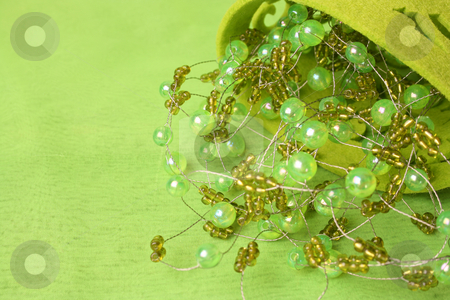 Beadwork stock photo, Green beadwork on a green background in a filt cup by Vanessa Van Rensburg