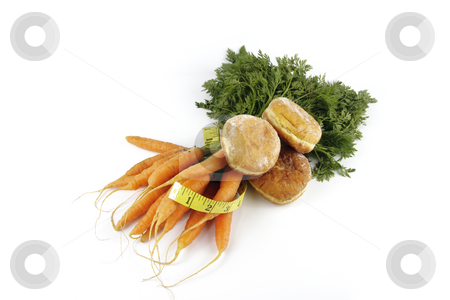 Carrots with Doughnuts and Tape Measure stock photo, Contradiction between healthy food and junk food using bunch of carrots and doughnut with a tape measure on a reflective white background by Keith Wilson