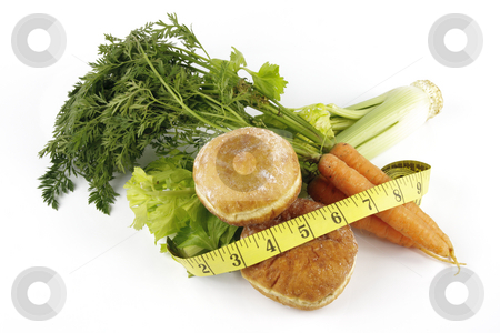 Carrots with Celery and Doughnuts stock photo, Contradiction between healthy food and junk food using a bunch of carrots and doughnuts with a tape measure on a reflective white background by Keith Wilson