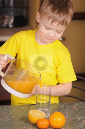 The child drinks juice stock photo, The child in a yellow vest drinks  orange juice by Salauyou Yury