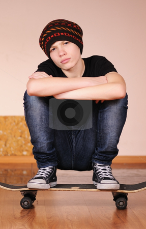The teenager with a skateboard  stock photo, The teenager with a skateboard and in a hat by Salauyou Yury