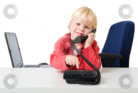 Boy on the phone stock photo, Young blond boy wearing a red sweater dialling on a phone in a sparce office by Corepics VOF
