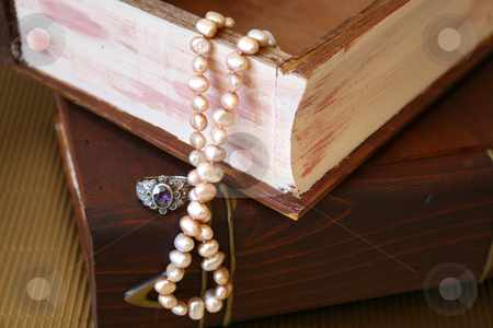 Pearls and a ring stock photo, Pearls and a silver ring with a purple stone on a wooden jewellery box by Vanessa Van Rensburg
