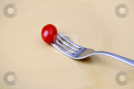 Single Tomato on fork stock photo, Single tomato on a fork against a yellow plate by Vanessa Van Rensburg
