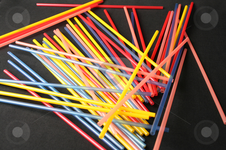 Coloured Straws stock photo, Various coloured toy straws on a black background by Vanessa Van Rensburg