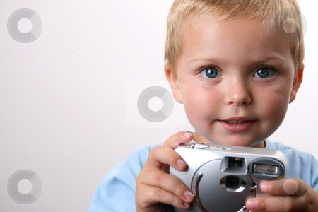 Photographer stock photo, Shy toddler holding a silver camera, looking at his object by Vanessa Van Rensburg