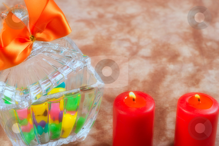 Romantic Candy stock photo, A romantic scene with a glass bowl full of candy with two lit red candles by Richard Nelson
