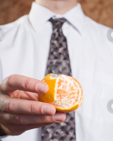 Peeled Orange stock photo, Closeup view of a businessman holding an orange that is partially peeled by Richard Nelson