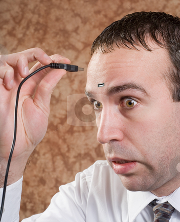 Data Man stock photo, Closeup of a young man about to insert a USB plug into his head by Richard Nelson