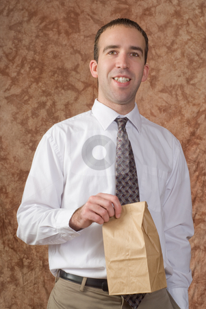 Employee Lunch stock photo, A young employee wearing a white shirt and tie, holding his paper bagged lunch by Richard Nelson