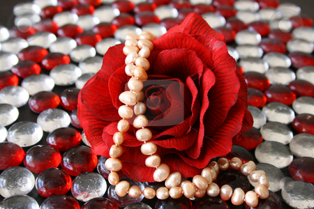 Pearls on a Rose stock photo, Artificial rose with real pearls on a surface of glass pebbles by Vanessa Van Rensburg