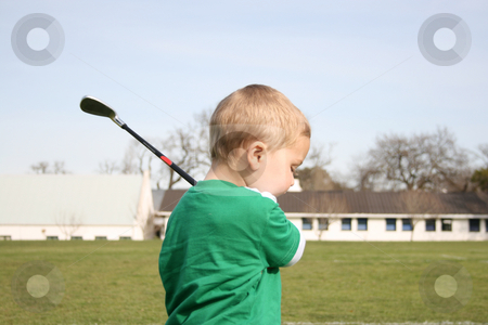 Golfing Toddler stock photo, Young boy practising golf on the driving range