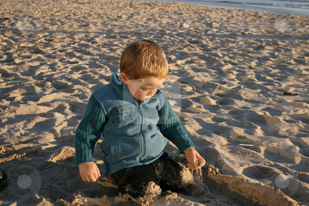 Playing stock photo, Young boy playing on the beach with the sand by Vanessa Van Rensburg