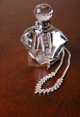 Diamond Necklace stock photo, Diamond necklace on a leather surface next to an empty perfume bottle by Vanessa Van Rensburg