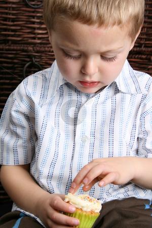Blond Boy stock photo, Beautiful blond boy busy eating a vanilla cupcake by Vanessa Van Rensburg