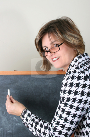 Beautiful School Teacher stock photo, Friendly School Teacher holding white chalk at the blackboard by Vanessa Van Rensburg