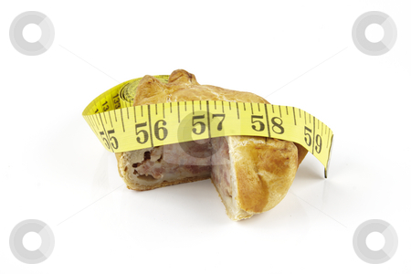Pork Pie and Tape Measure stock photo, Single golden pork pie and yellow tape measure on a reflective white background by Keith Wilson