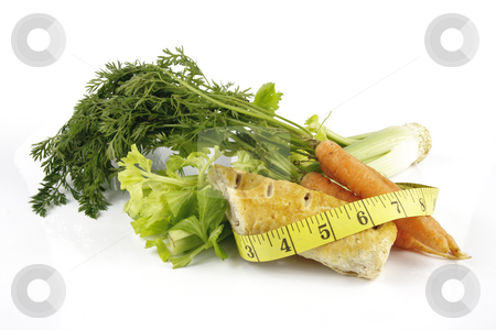 Carrots with Celery and Sausage Roll stock photo, Contradiction between healthy food and junk food using a bunch of carrots and sausage roll with a tape measure on a reflective white background by Keith Wilson