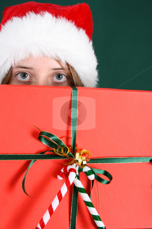 Christmas Present stock photo, Brunette Teenager peeping out behind a present by Vanessa Van Rensburg