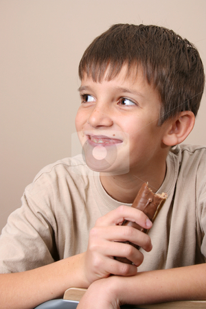Chocolate Kids stock photo, Young boy with big eyes, eating a chocolate bar by Vanessa Van Rensburg