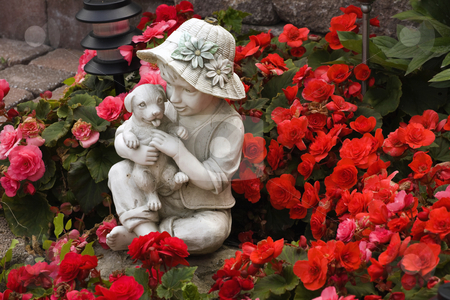 Flower Bed stock photo, Small statue in flower bed by David Chapman