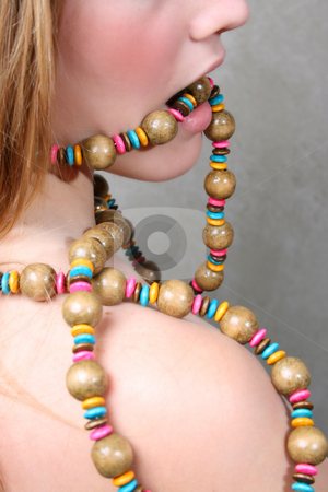 Female Model stock photo, Beautiful female model a string beads in her mouth by Vanessa Van Rensburg