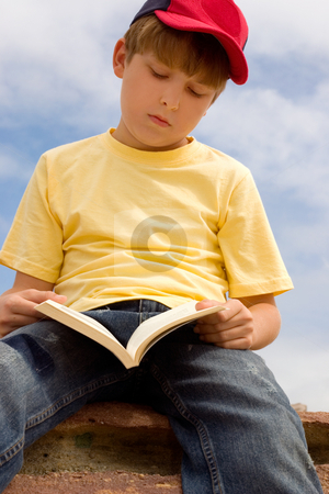 Booklover stock photo, Child passing time, reading a book in the sunshine by Leah-Anne Thompson