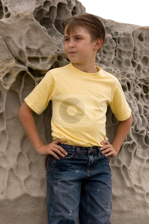 Confident Gaze stock photo, Nine year old boy wearing t-shirt and denim jeans standing by weathered rocks by Leah-Anne Thompson